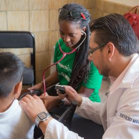 A student on a spring break trip in Mexico checks a child's vital signs during a Public Health outreach.